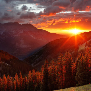 <p>A brilliant sunset beams through the Uncompahgre River valley. The town of Ridgway is located below the sunset; Ouray would be down in the valley to the left. As seen from along the Horsethief Trail, August.</p>